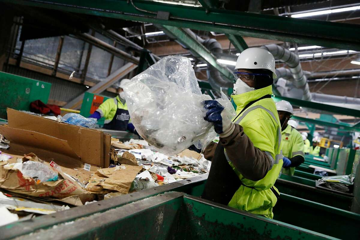 Tyrell Jones, material handler, removes plastic bags from a conveyor belt at Recology's Recycle Central on Monday, September 30, 2019 in San Francisco, CA.