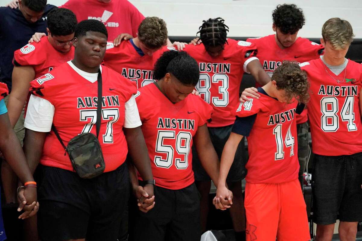 Kendal Septs, 18, left, (77) a senior, and other football players pray for his cousin, Jordyn Hawkins, during a prayer rally. The 15-year-old football player at Fort Bend's Austin High School was left paralyzed after suffering a spinal cord injury during a game.