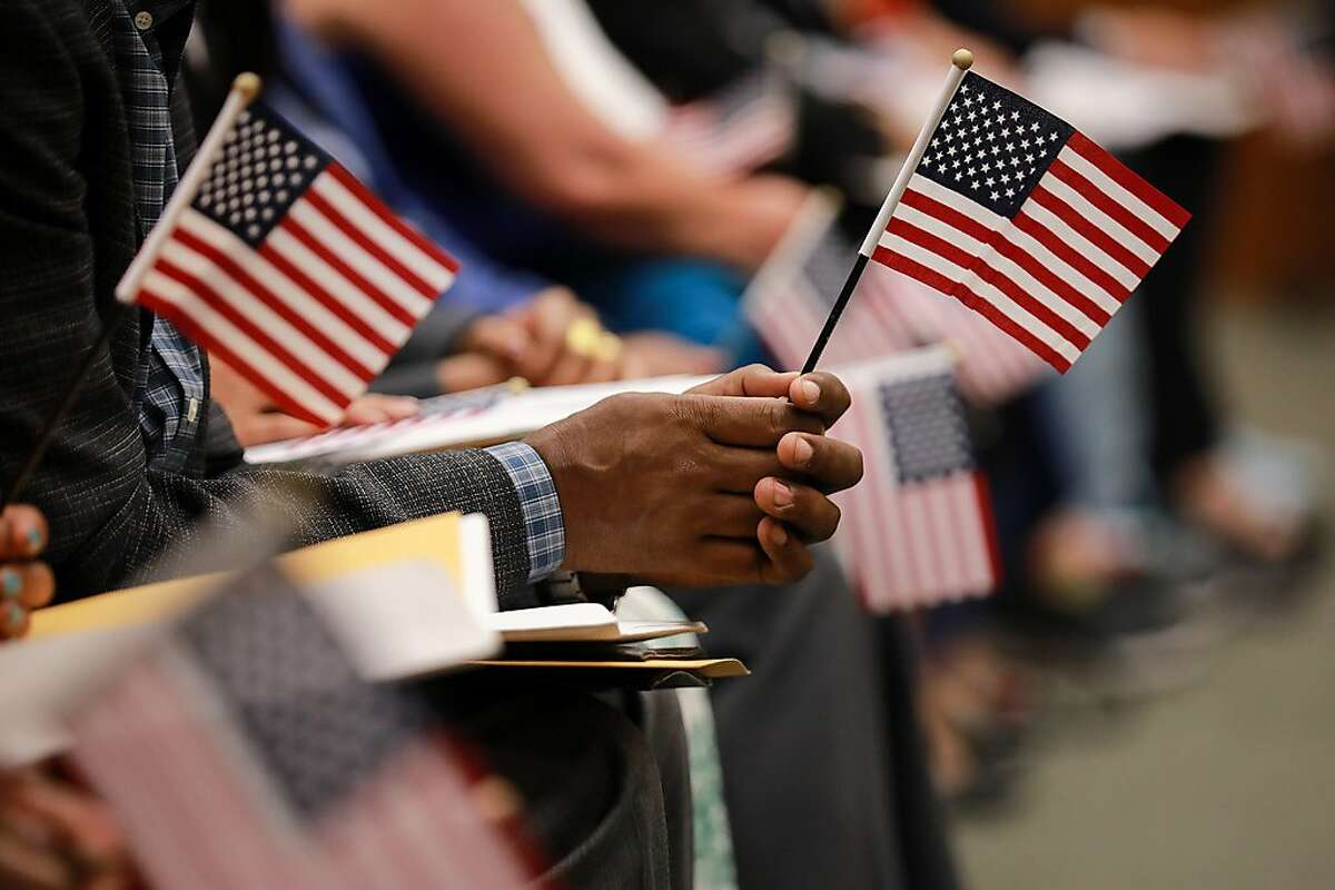 Immigrants hold on to American flags ahead of their naturalization ceremony in Washington, Sept. 10, 2019. The U.S. population gained immigrants last year at the slowest pace since 2008. President Donald Trump's approach to immigration is seen as the likely cause. (Amanda Andrade-Rhoades/The New York Times)