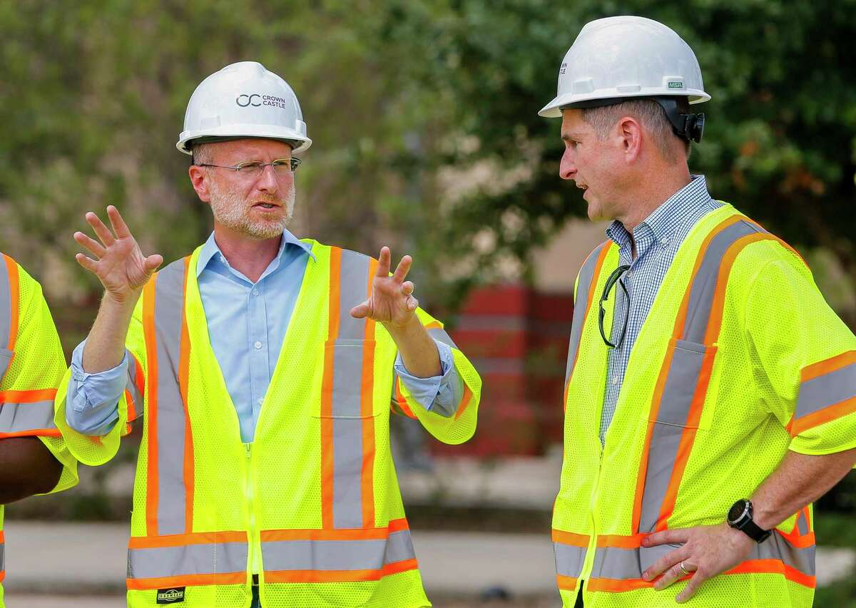 Brendan Carr (left), Commissioner of the Federal Communications Commission (FCC), speaks with Mike Kavanagh (right), Senior Vice President, Sales and Chief Commercial Officer of Crown Castle, at a site where work is underway to finish installing fiber that will one day support a 5G network, near Guadalupe Plaza Park in Houston's Second Ward, Monday, Sept. 30, 2019.
