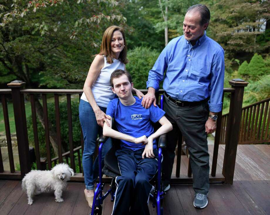 Phil and Andrea Marella with their son, Andrew, 20, and dog, Lacy, at their home in Greenwich. Andrew has a rare progressive genetic disorder called Niemann-Pick disease type C (NPC), which took the life of his sister, Dana, in 2013. The Marella's non-profit Dana?'s Angels Research Trust (DART) raises money to research the disease and is holding the DART to the Finish charity walk at Greenwich Point Park on Saturday, Oct. 5. Photo: Tyler Sizemore / Hearst Connecticut Media / Greenwich Time
