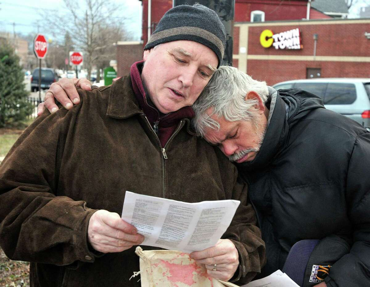 New Haven--Mark Colville, left, and Edwin Irrizarry, both of New Haven, hug during a prayer during a rally to stop deportations held by local community action groups and churches at the Kimberly Triangle Park. Photo-Peter Casolino 03/01/12