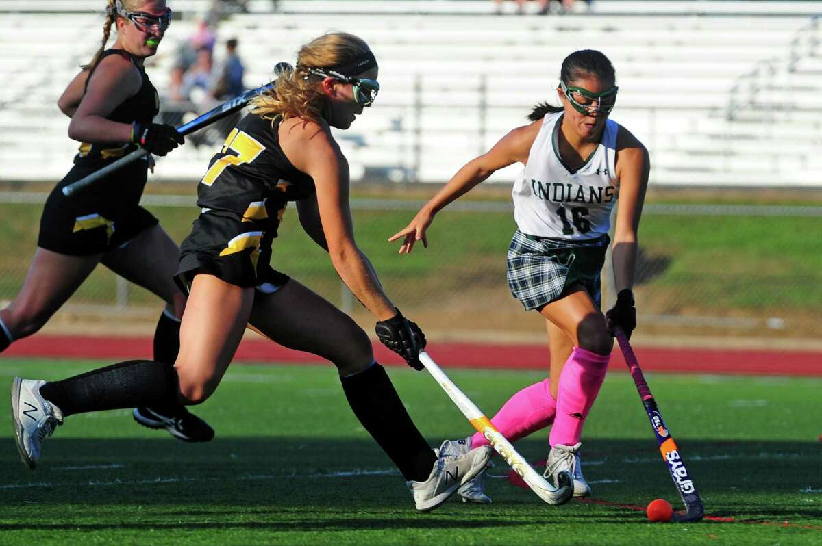 Hand's Grace Hartmann, left, and Gilford's Cat Larrow converge on the ball during field hockey action in Guilford on Oct. 1.
