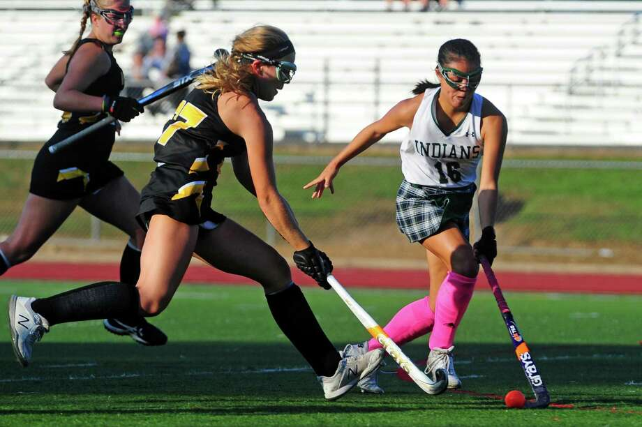 Hand's Grace Hartmann, left, and Gilford's Cat Larrow converge on the ball during field hockey action in Guilford on Oct. 1. Photo: Christian Abraham / Hearst Connecticut Media / Connecticut Post