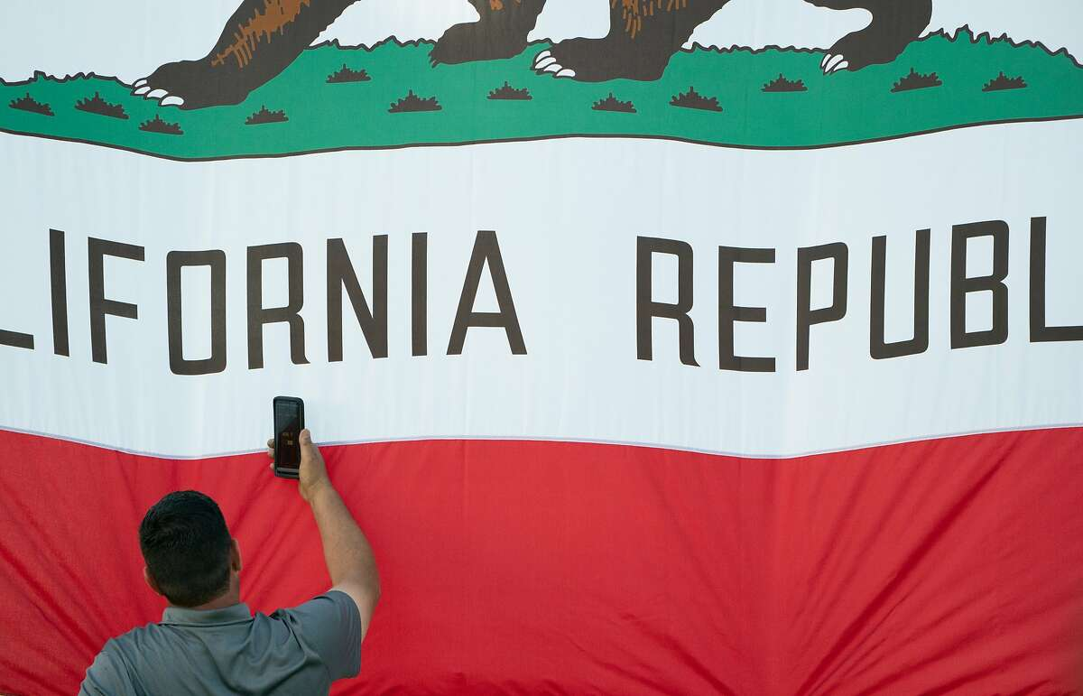 A man photographs the state flag at Laney College in Oakland on May 31, 2019. California's population shrank slightly last year, the first time the state has measured an annual decline in decades of tracking.