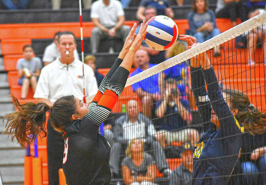 Edwardsville's Rhianna Huebner, left, wins a point at the net for the Tigers in the first game against the O'Fallon Panthers on Tuesday in Edwardsville. Photo: Matt Kamp|The Intelligencer