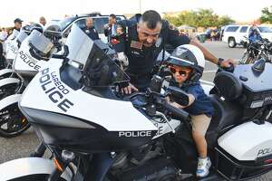 Officer Mario Bernal shows Deandre Gomez how to use the sirens on a Laredo Police Motorcycle at the Sames Auto Arena during the National Night Out Law Enforcement Expo.