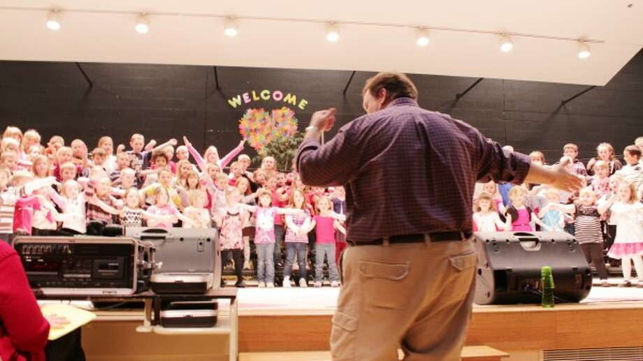 Kindergarteners sing under the direction of Music teacher Phil David.