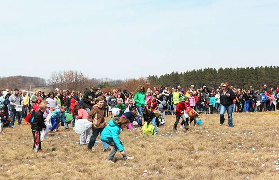 FILLING BASKETS: Thousands of children attended this year's Evart Easter Egg Drop, which took place on April 19. A total of 16,000 eggs were snatched up by children of all ages. (Herald Review photo/Karin Armbruster)
