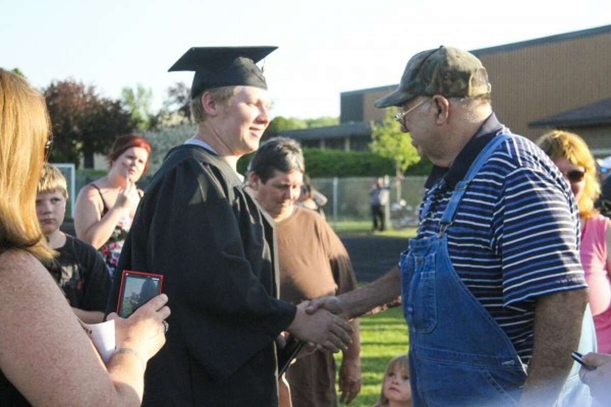 FAMILY: Kalub Robinson receives a hand shake from his grandfather after graduation. (Herald Review photo/Emily Grove-Davis)
