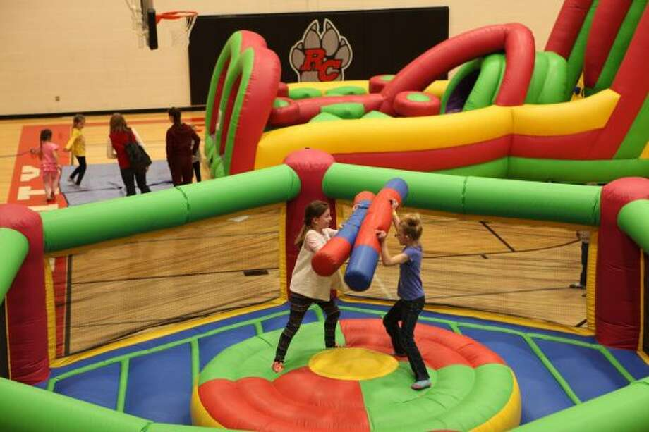 During the Reed City Band Carnival, Gabby (left) and Charity Rogers go head-to-head in an inflatable gladiator-style game. The game was one of the many highlights of the carnival. (Herald Review photo/Meghan Gunther-Haas)