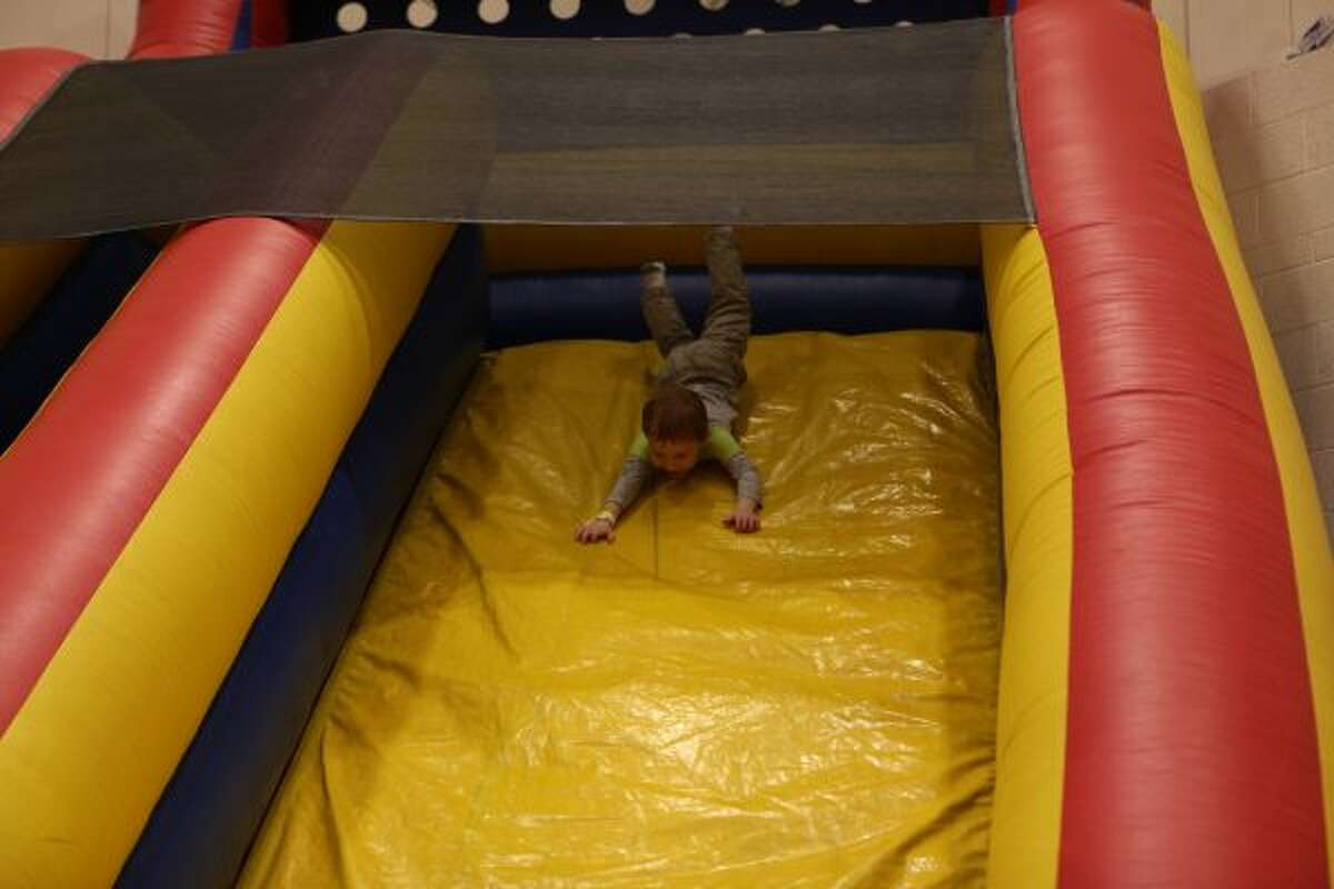 Throughout Saturday afternoon, children raced up and found creative ways down a large inflatable slide set up in the high school gymnasium. One carnival-goer, Ryder Holmes slid down the slide head first.