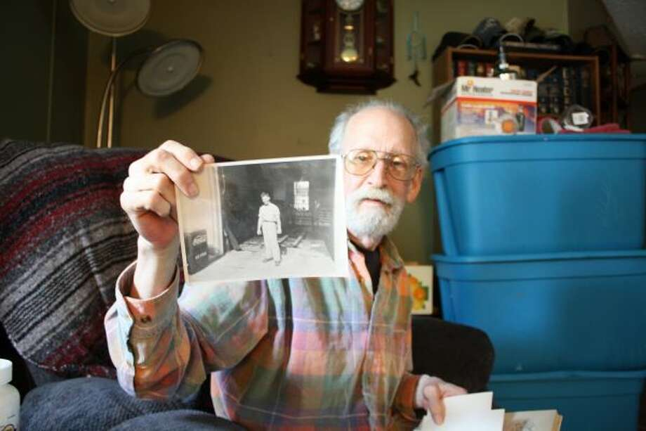 Larry Conrad holds up a photo of his father. The photo, along with others, was inside a baby book recently returned to him by Linda Phelps, of London, England. (Herald Review photo/Candy Allan)