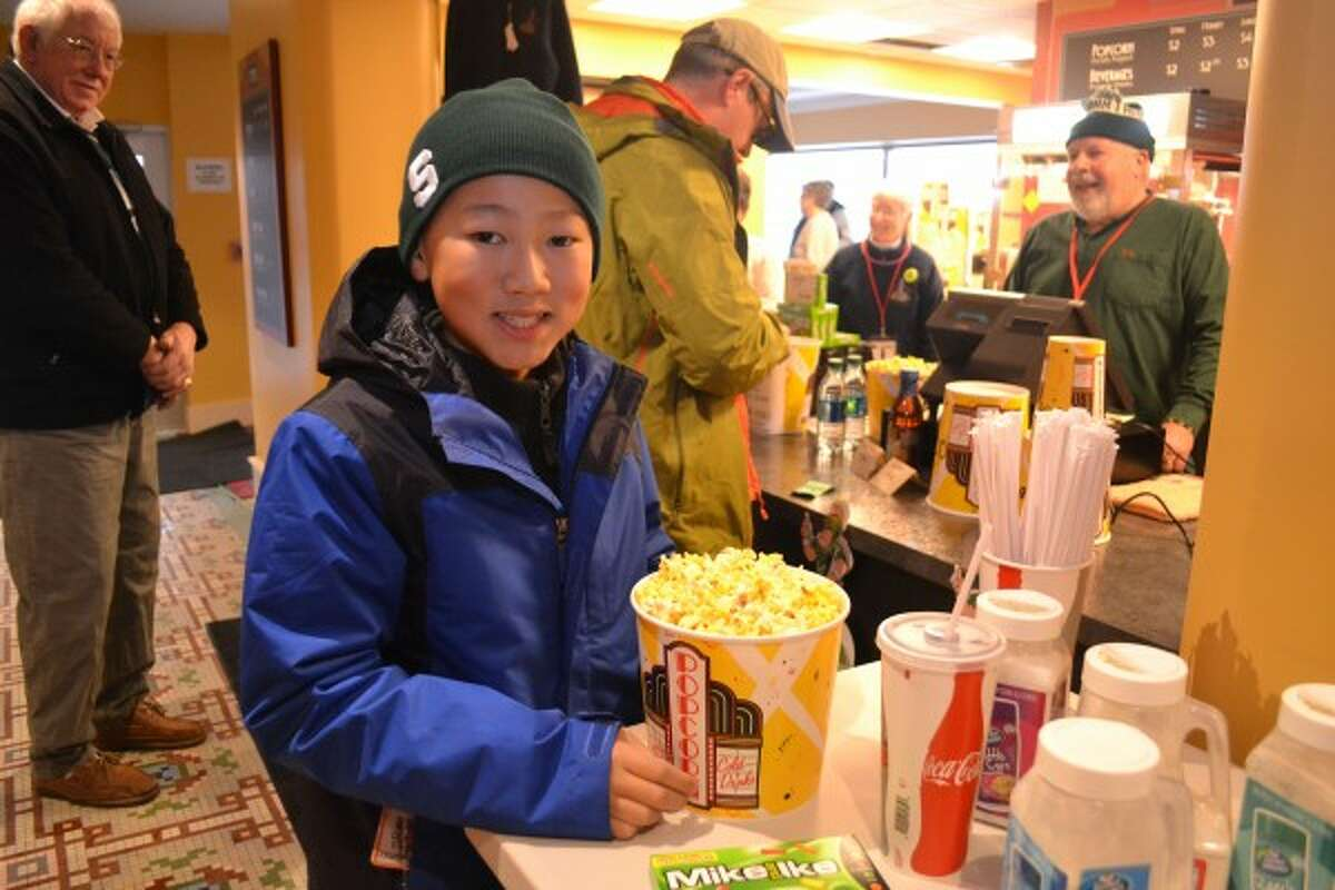 William Albee (foreground) buys popcorn from the Vogue Theatre's concession stand before the beginning of the Michigan State game on Wednesday evening. (Meg LeDuc/News Advocate)