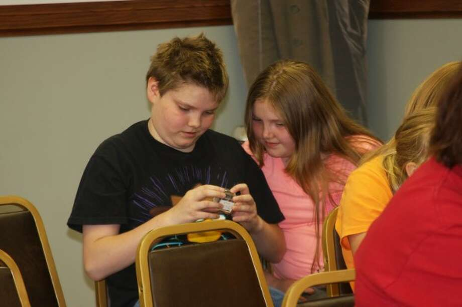 Logan and Elyssa Miller, of Eastlake, check out a preserved bug during Bug Science at the Manistee Library on Wednesday. (Justine McGuire/News Advocate)