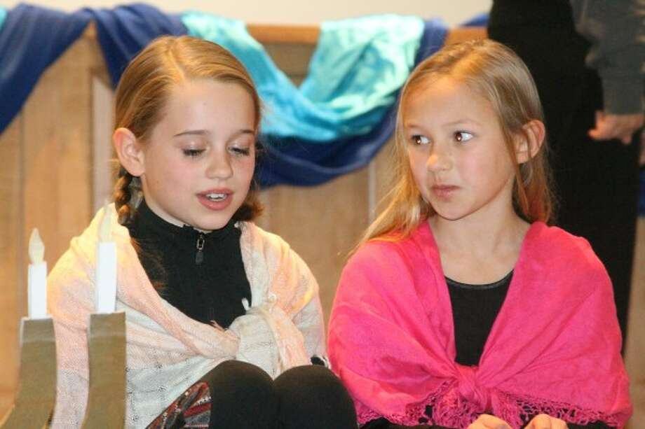 Ce-Ce Postma and Laura Eix, members of the Faith Covenant Church Children's Choir, pretend to be poor children during Hanukkah during a singing skit at a community women's event at the church on Tuesday. (Justine McGuire/News Advocate)