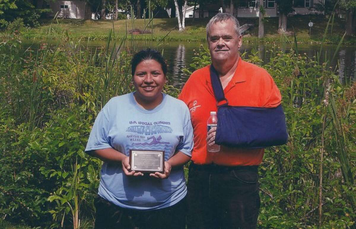 Gary Boerema presents Lupe Covarrubias with an award for 2014 Area 24 Special Olympics Inspirational Athlete of the Year.