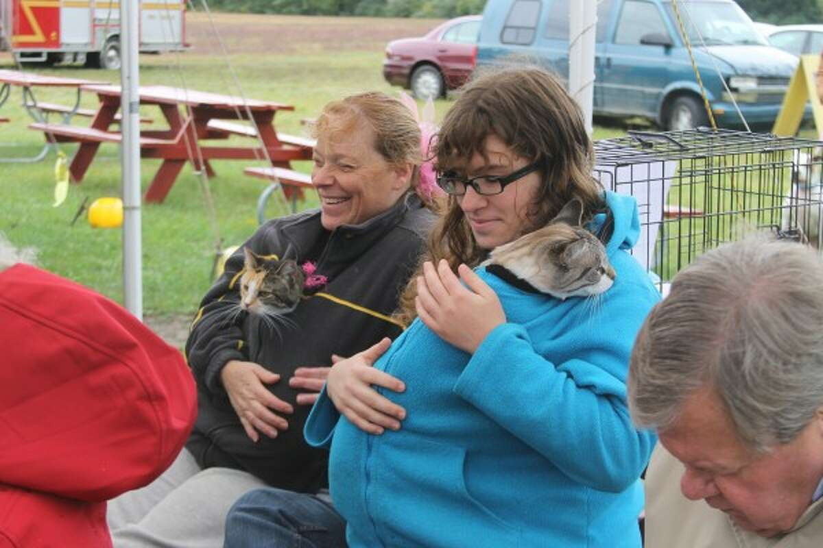 Celeste Barnes (left) and Brittany Strickler try to keep their feline friends, Calypso and Dough Boy, warm during the Blessing of the Animals on Sunday at Circle Rocking S Children's Farm in Free Soil. (Michelle Graves/News Advocate)