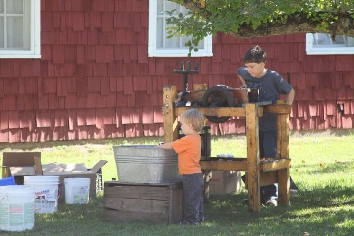 Brenden Brady, 9, of Manistee, turns the crank of an apple cider-making machine while Andrew Salmon, 3, of Manistee, plays with apples at the Spirit of the Woods Conservation Club's 75th anniversary open house on Saturday. (Justine McGuire/News Advocate)