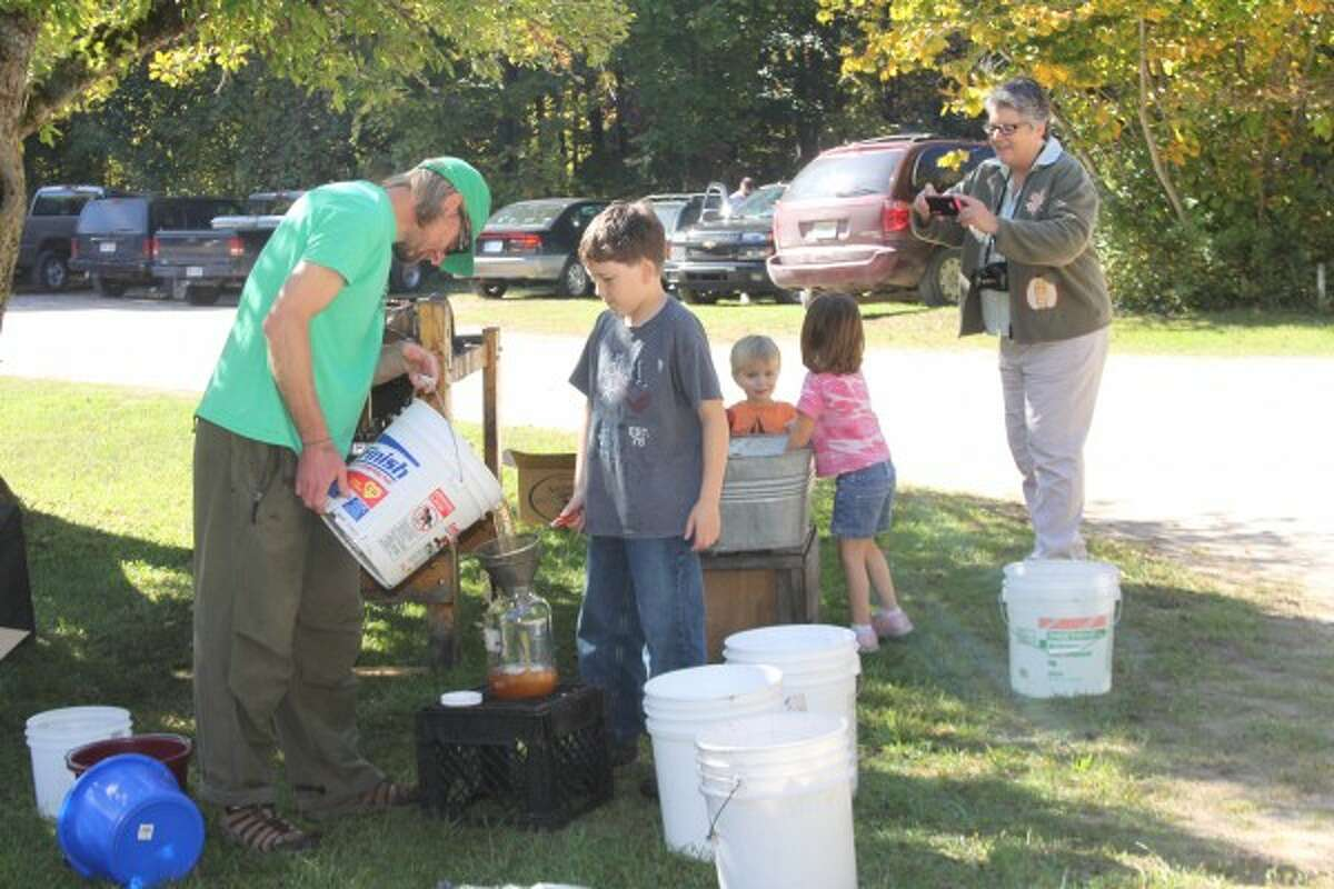 Spirit of the Woods Conservation Club president Erik Kinzinger shows Brenden Brady, 9, of Manistee, how to make apple cider at the club's 75th anniversary open house on Saturday. (Justine McGuire/News Advocate)