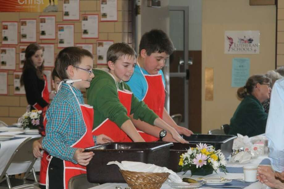 Trinity Lutheran School students clear tables while volunteering during the Pork Roast and Sauerkraut Supper at Trinity Lutheran School's gym on Saturday. Pictured are Miles Bednarczyk, Adam Fennell and Ethan Nickelson. (Justine McGuire/News Advocate)