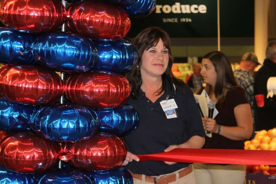 A Manistee Meijer employee holds the ceremonial ribbon prior to the ribbon cutting at the new store on Thursday. (Justine McGuire/News Advocate)