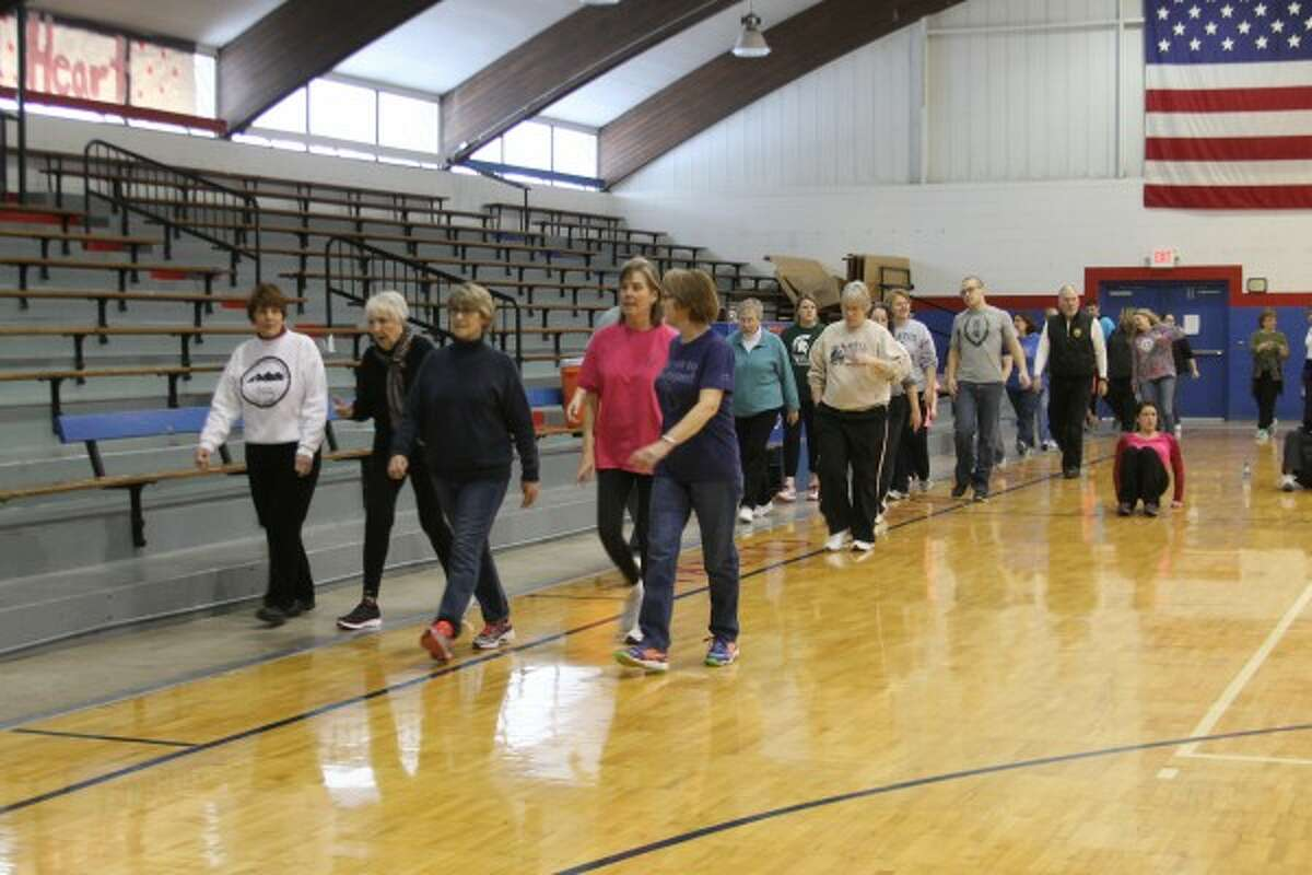 More than 150 people walk around the Manistee Catholic Central gym during a ViSalus event that was part of a world record attempt for the largest simultaneous workout group on Saturday. (Justine McGuire/News Advocate)