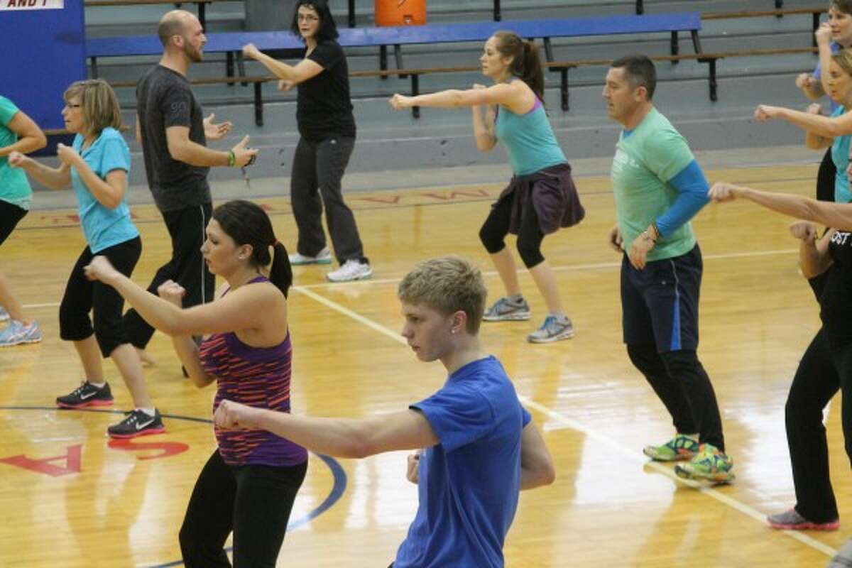 A group works on a variety of exercises in the middle of the Manistee Catholic Central gym during a ViSalus event that was part of a world record attempt for the largest simultaneous workout group on Saturday. (Justine McGuire/News Advocate)