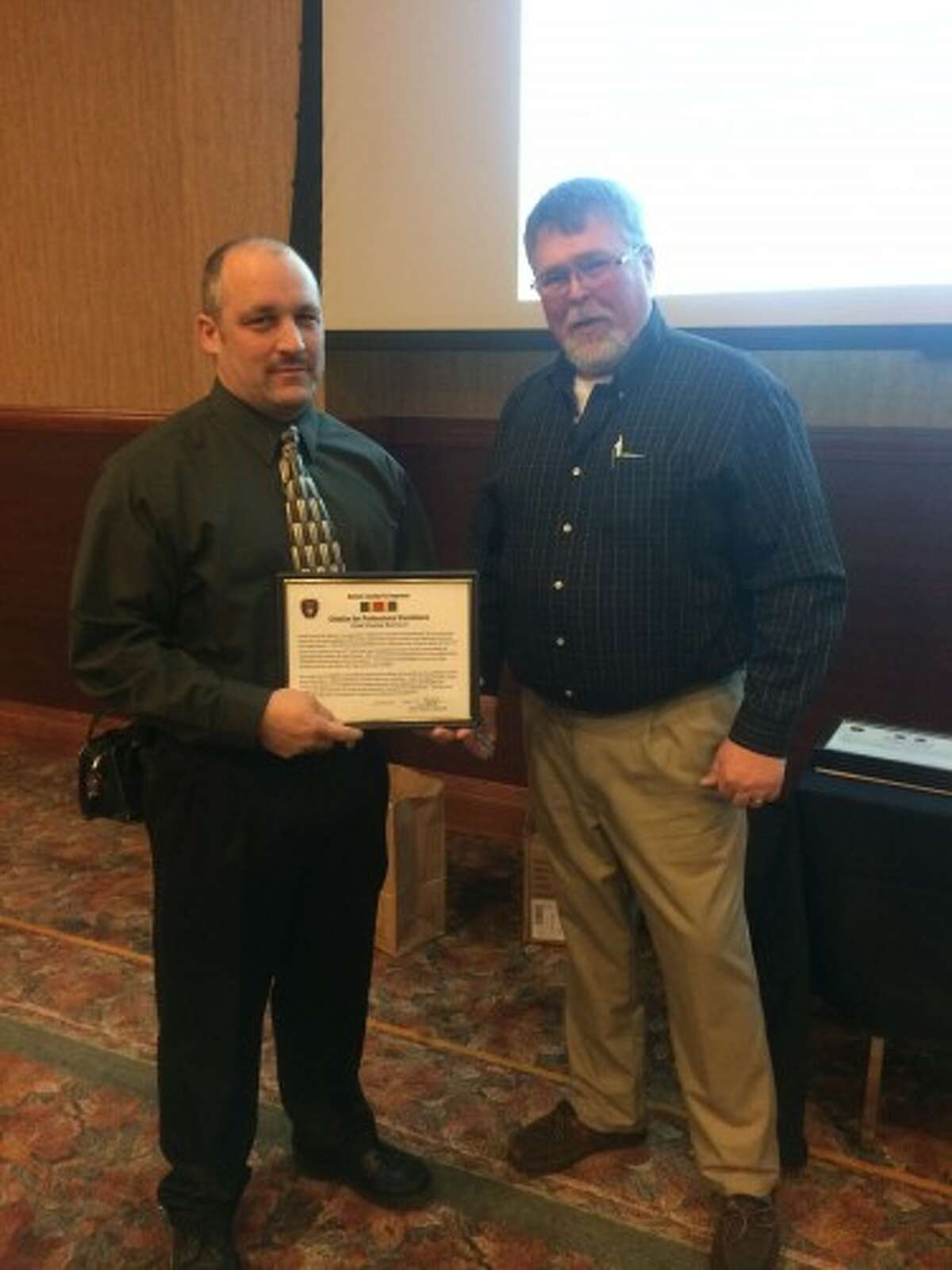 """Chief Charles Barron of the Manistee Township Fire Department accepts an award in """"Citation of Professional Excellence"""" from Dennis Bjorkquist, township supervisor, on behalf of the staff of the fire department. (Courtesy photo)"""