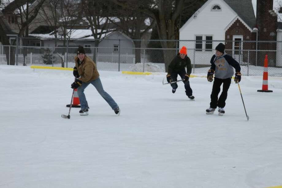 Since the ice rink opened at Sands Park on Friday, about 150 people have put it to use, including a group playing hockey on Sunday. (Photos by Ken Grabowski/News Advocate)