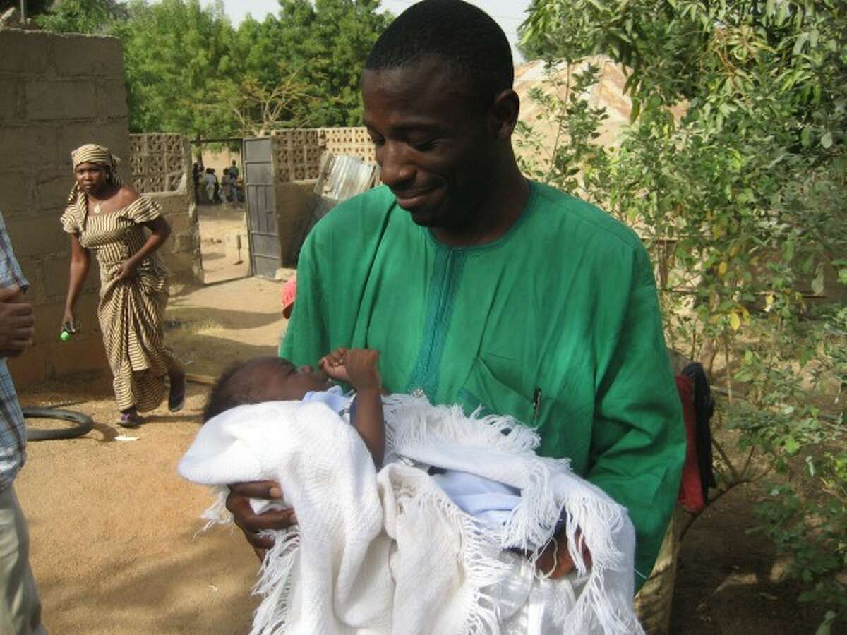 Roger Bruce / Courtesy Photo Joshua Ishaku (pictured) holds his new niece for the first time 2009 in Lassa, Nigeria. From Maiduguri, Nigeria, Ishaku was one of the Nigerians in in the Church of the Brethren work camp Joseph was a part of.