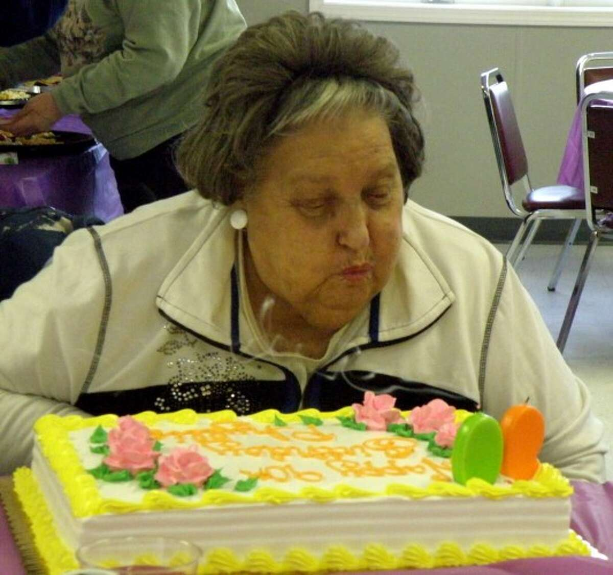 Phyllis Sheras blows out the candles on her birthday cake as she celebrates her 90th birthday at the Manistee Senior Center. (Jeanne Barber/Courtesy photo)