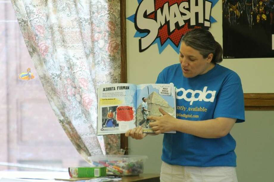 Andrea Cosier, youth services director at the Manistee County Library, reads from a book about world record holders during the Sports Heroes Challenge at the Manistee Library on Thursday. (Justine McGuire/News Advocate)