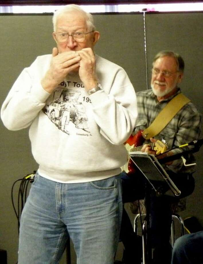 """Jack Hanson, with his harmonica, joins the D-Notes in a rollicking version of """"She'll Be Coming 'Round the Mountain"""" during Toe Tapping Tuesday at the Manistee Senior Center. (courtesy)"""