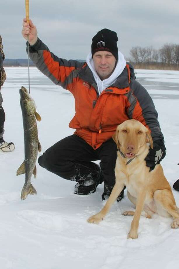 Mark Cameron, of Manistee, holds up a pike he speared in his shanty on Manistee Lake on Friday with the help of his dog, Molly. (Justine McGuire/News Advocate)