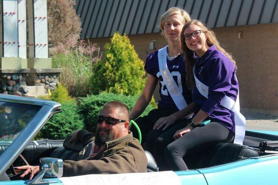 Teacher and girls basketball coach Tim Reznich drives junior homecoming reps Edvard Bilk and Sydney Miller in the homecoming parade. (Photo/Robert Myers)
