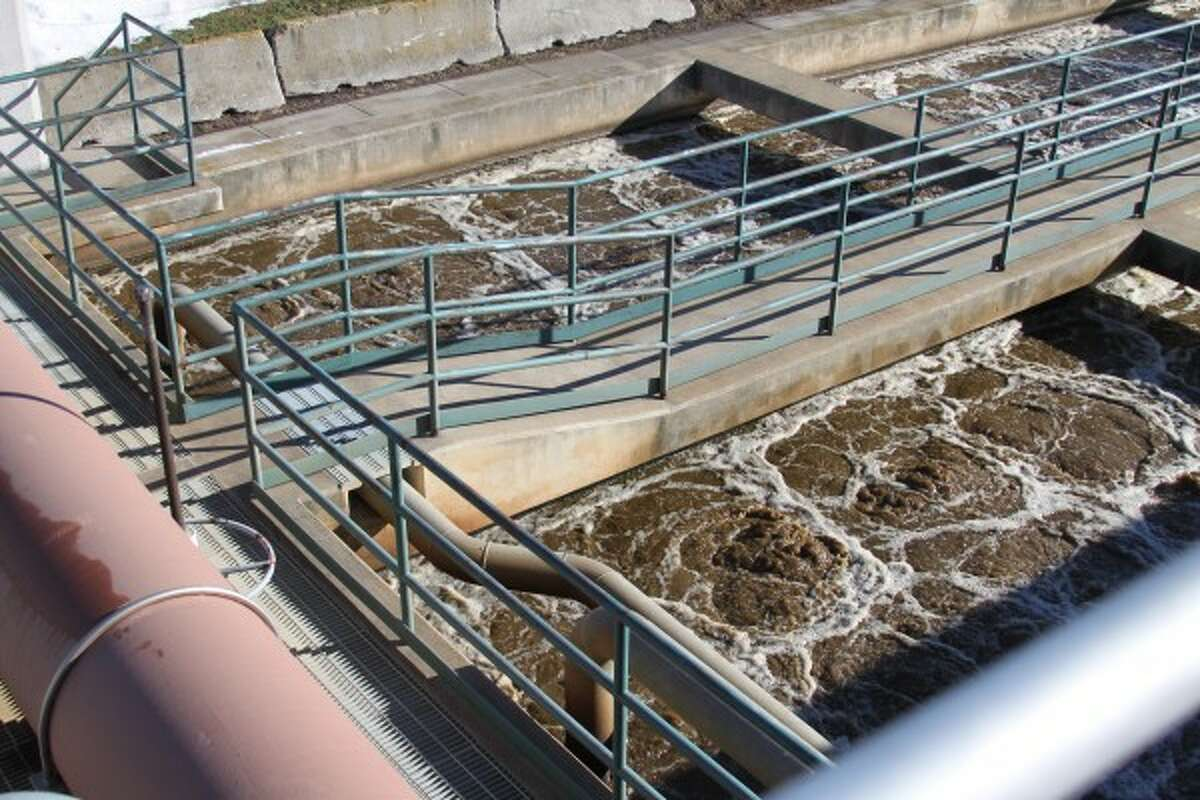 """The water in the aeration basins bubbles because of added air to the sewage to oxidize it, mixed with activated sludge. Mikula said """"bugs"""", or microorganisms, are added to the water. The """"bugs"""" eat the sewage in the water. """"(The bugs) stop eating and go into huge tanks called clarifiers,"""" he said. """"We add polymers, which make the bacteria get heavy and it goes to the bottom and the clean water is skimmed from the top."""" (Sean Bradley/News Advocate)"""