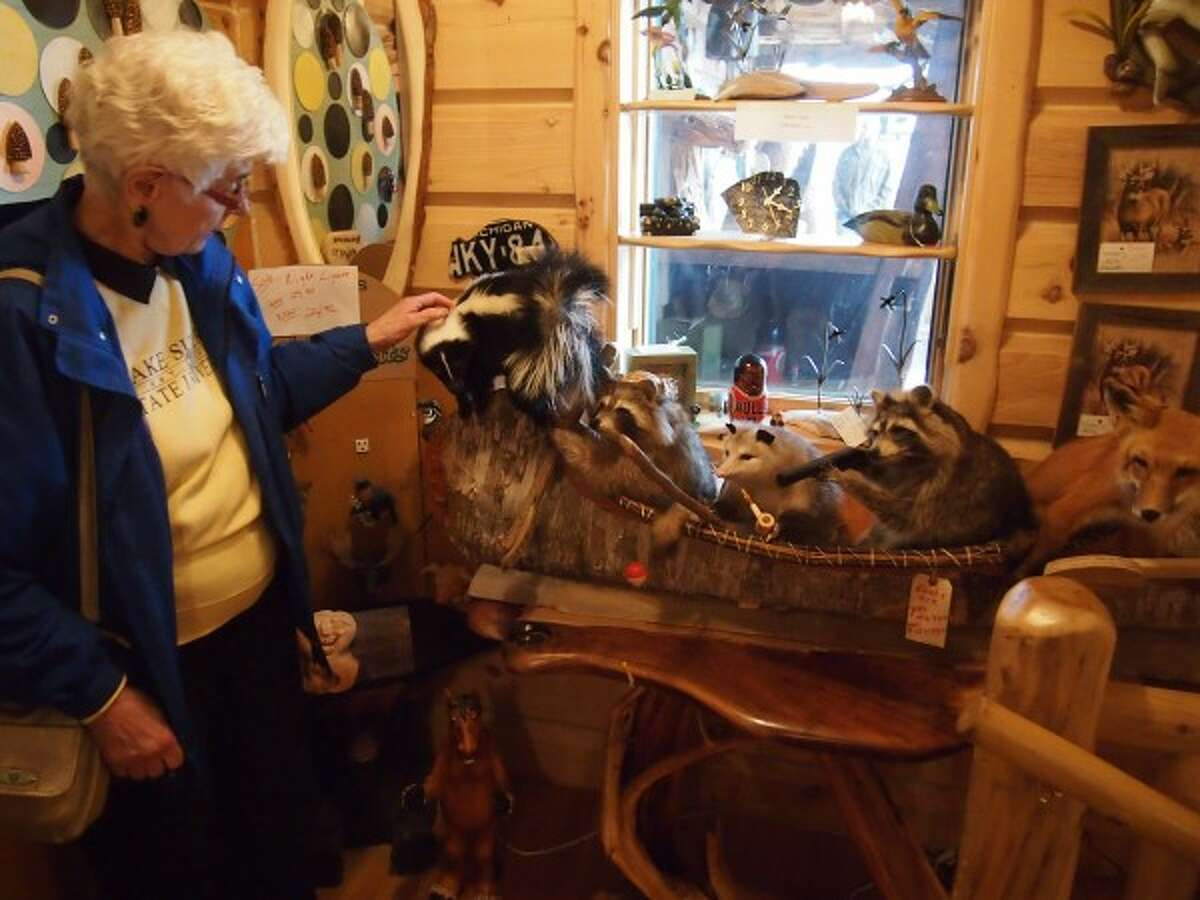 Marge Hybza checks out a replica of canoe filled with stuffed animals at the Wolf's Den during the senior center's Mystery Trip on Thursday. (Courtesy photo/Jeanne Barber)