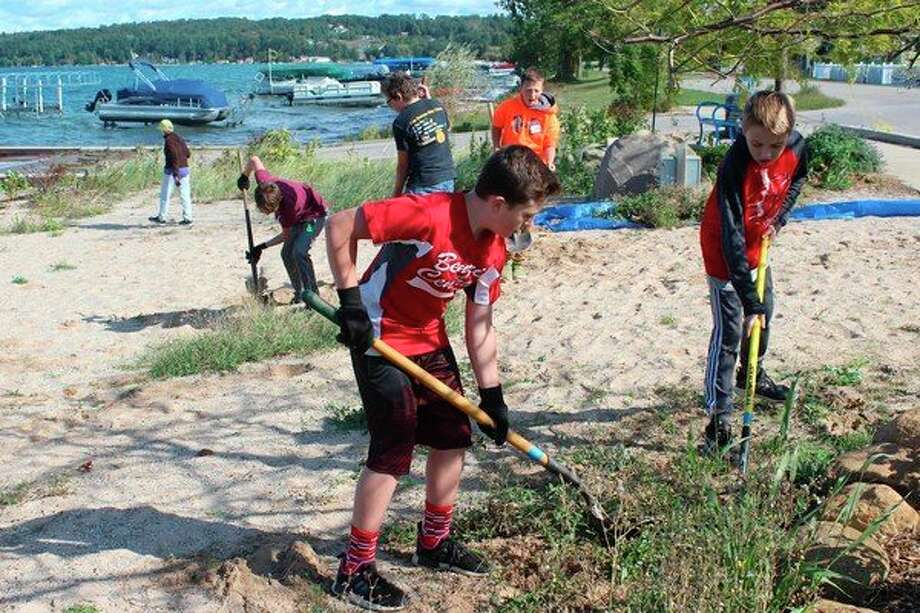Benzie Central seventh graders work to clean up properties managed by the Village of Beulah. (Photo/Robert Myers)