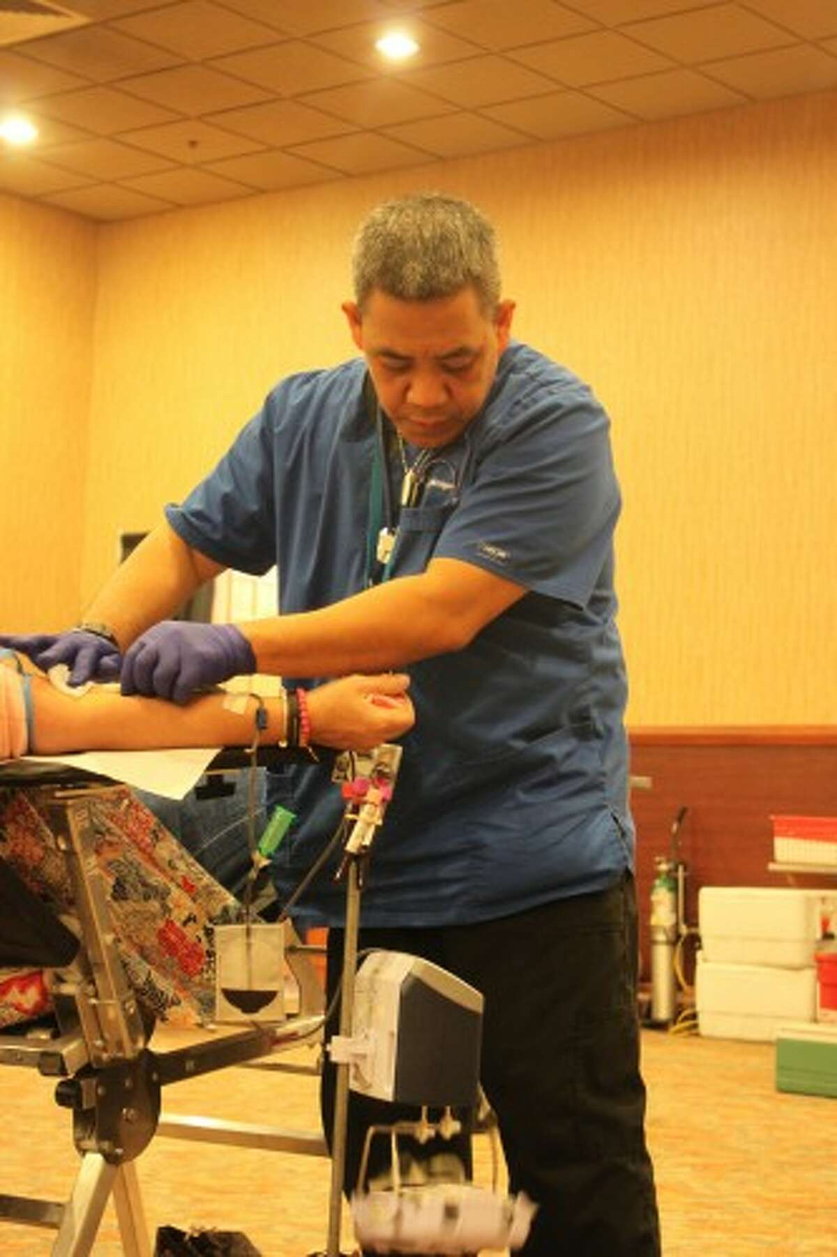 After drawing blood from Benzonia resident Ola Reed Wednesday during a blood drive at Little River Casino Resort in Manistee, Michigan Blood phlebotomist Ben Ramos puts a cotton ball over her arm then applies a Band-Aid. (Sean Bradley/News Advocate