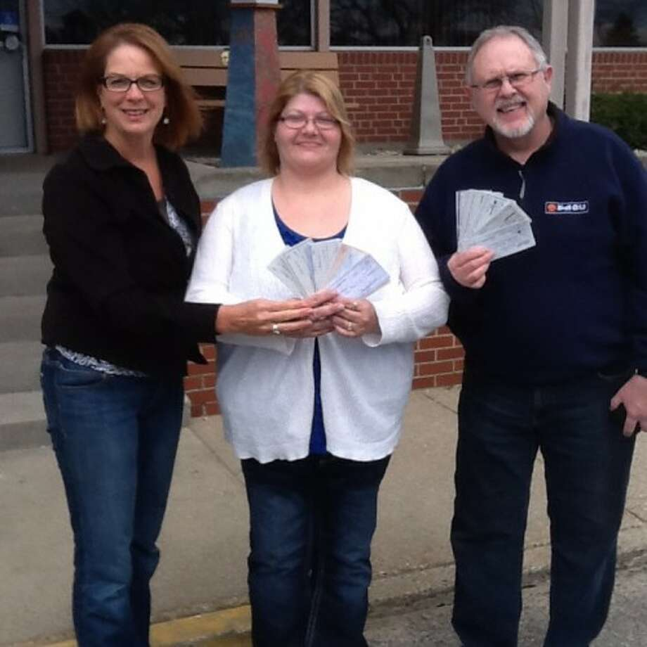 Judy Crockett, co-founder of 100 Women Who Care Manistee County, poses with Angela Beneke and Mike Woroniak, of StonesHouse Recovery of Manistee County, as they fan out checks donated to StonesHouse through the care group's second quarter meeting last week. (Courtesy photo)