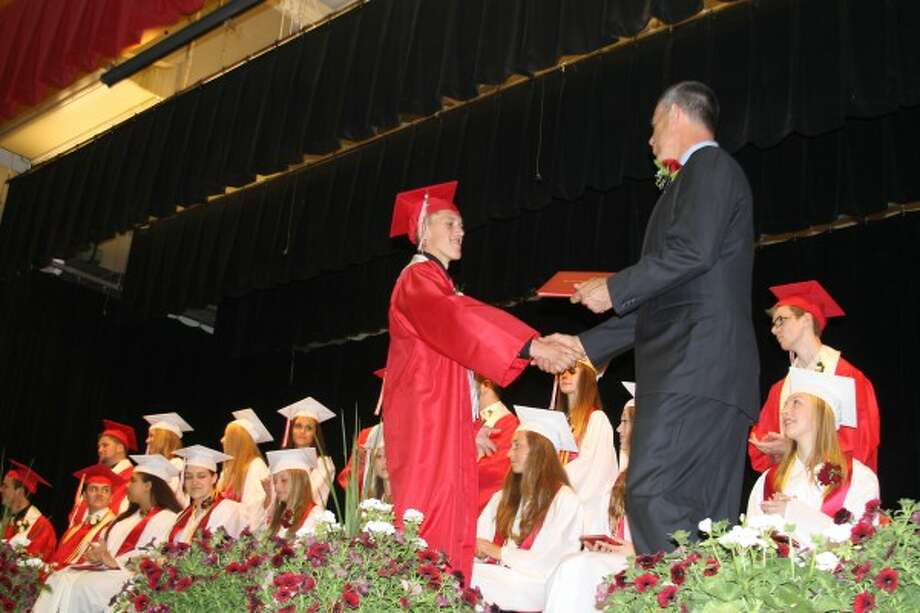 Taylor Makowski shakes hands with the Bear Lake School Board president as he receives his diploma after walking across the Bear Lake High School stage at commencement on Sunday. (Justine McGuire/News Advocate)