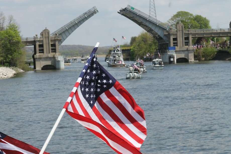 The last boats in the Tight Lines for Troops flotilla pass under the U.S. 31 bridge in Manistee on Saturday as residents wave American flags to welcome them to port.