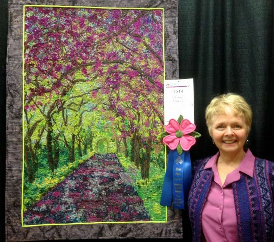 """Arcadia resident Sally Manke poses with her award-winning art quilt, """"Spring Stroll,"""" which won first place in April at the American Quilt Society (AQS) event in Paducah, Ky., in the small wall quilts fiber art category. The quilt is made from pieces of batik (a material used to make the quilts made from dyes and waxes) covered with tulle, which is a fine netting that holds down the batting in the quilt. She said it took 10 days to create. (Courtesy Photo/News Advocate)"""