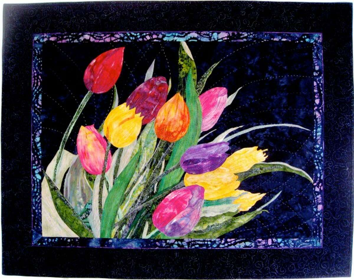 """Manke's """"Wind Tossed Tulips"""" art quilt is based on tulips planted in split stone flower beds her husband Patrick built. """"Each colorful blossom, green leaf and stems are cut from my stash of hand dyed and batik fabrics,"""" a description on her Etsy page indicated. """"They are layered then bonded to the midnight blue batik background. An assortment of threads quilt the bouquet to the backing, batting and background fabric. The piece was juried and accepted at the International Quilt Association Houston Quilt Show and Market. (Courtesy Photo/News Advocate)"""