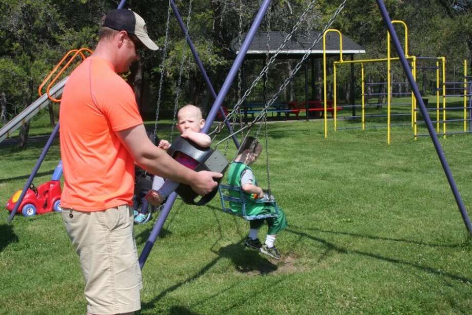 Travis Walker plays with his daughter, Hadley, on the swings on Wednesday at Stronach Park during the Playgroup at the Park event. (Ian Bergel/Pioneer News Network)