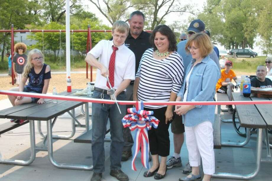 "Patrick Knechtges, the son of the late Richard Knechtges, cuts the ribbon to formally open Rotary ""Rocket"" Park Friday in Manistee. Alongside him are (left to right): City of Manistee Department of Public Works director Jeff Mikula; Rotary of Manistee co-president Anna Mann; former City of Manistee manager and Rotary of Manistee co-president Mitch Deisch and City of Manistee mayor Colleen Kenny. (Sean Bradley/News Advocate)"
