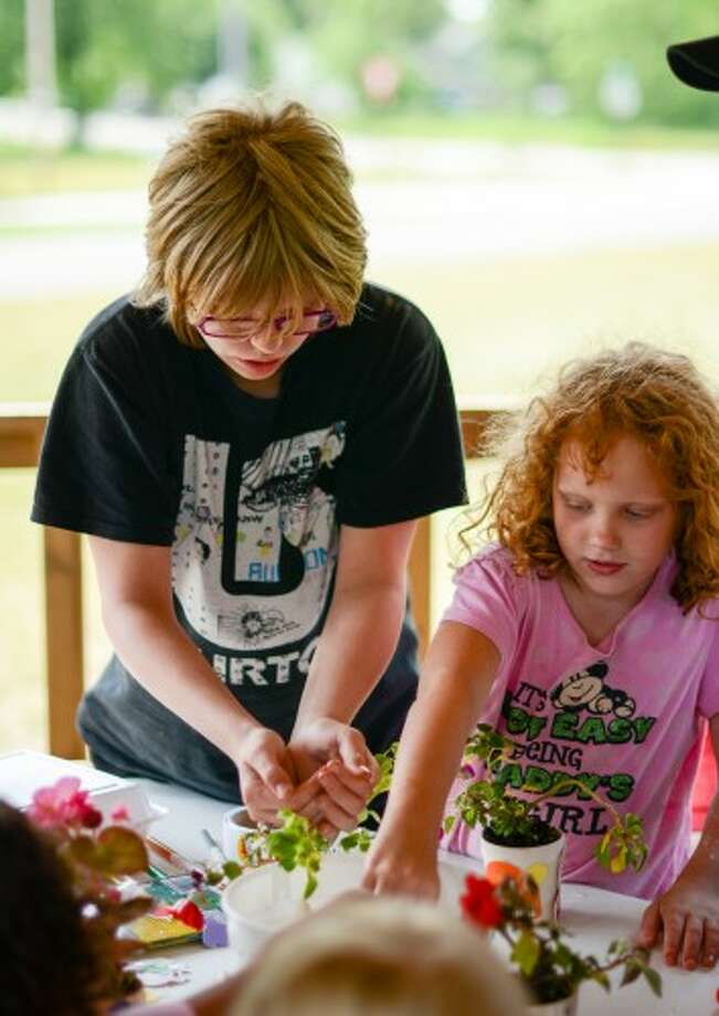 (From left) Heaven Cerka, 13, of Manistee, and her sister, Izabella, 9, plant begonias at the gazebo next to the Kaleva Library. (David Navadeh/News Advocate)