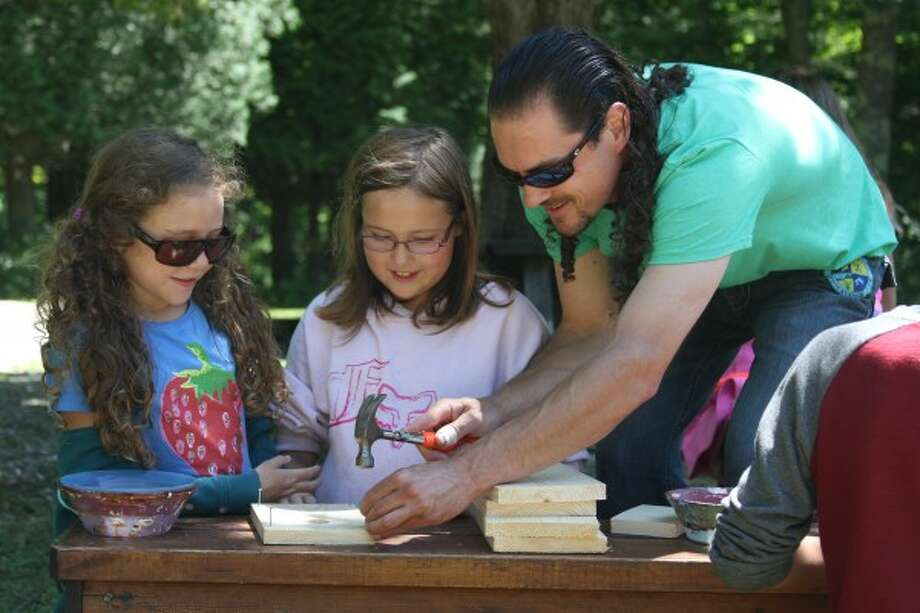 Camp counselor Rob McMurry helps campers Hazel Groves (left) and Madisyn Parks build a birdhouse on Wednesday during the 20th annual Field Camp put on by the Spirit of the Woods Conservation Club of Brethren. (Dylan Savela/News Advocate)