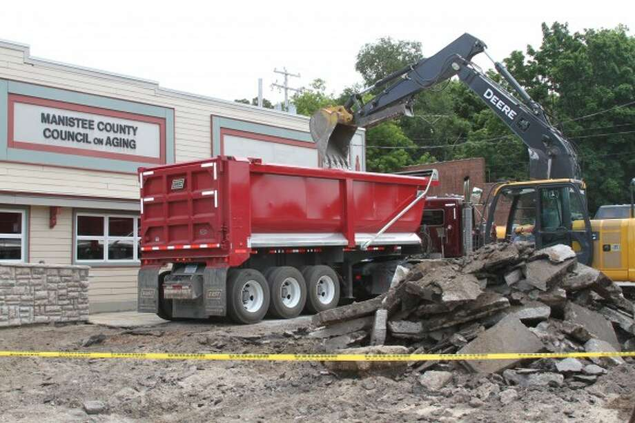 Crews from Swidorski Bros. Excavating LLC and Patrick Swidorski Trucking LLC work to remove asphalt from the Manistee Senior Center parking lot on Thursday. (Dylan Savela/News Advocate)